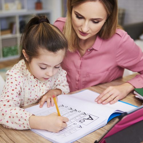 Young woman helping girl with homework
